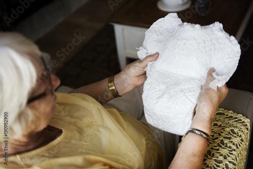Fotografiet  Senior woman looking at a diaper
