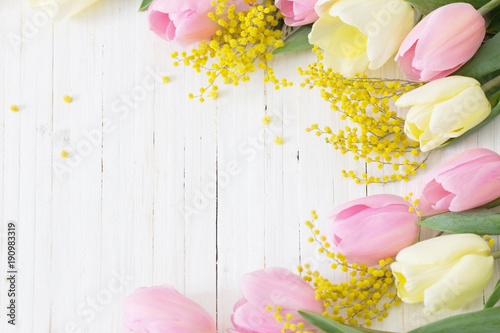 mimosa and tulips on white wooden background