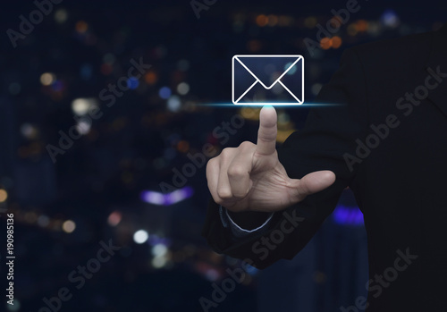 Businessman pressing mail flat icon over blur colorful night light city tower, Contact us concept