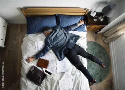 Exhausted business man falling asleep as soon as he came back home Canvas Print
