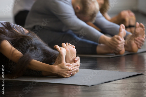 Recess Fitting Yoga school Group of young sporty people practicing yoga lesson with instructor, sitting in paschimottanasana exercise, Seated forward bend pose, working out, students training in club, indoor, studio close up