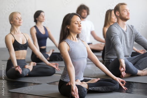 Staande foto Lotusbloem Group of young sporty people practicing yoga lesson with instructor, sitting in Padmasana exercise, Lotus pose, working out, indoor full length, students training in club, studio