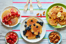Homemade Pancakes With Strawberry, Banana, Blueberry, Cashew, Almond And Honey On White Table. Family Breakfast For 3 Person.