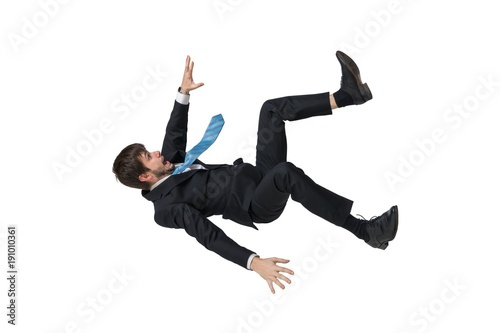 Obraz Young businessman falling down in free fall. Isolated on white background. - fototapety do salonu