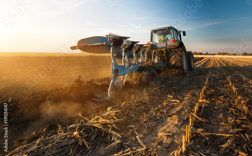 Tractor plowing fields -preparing land for sowing in autumn Canvas Print