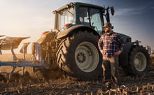 Farmer Working During The Tractor Plowing Fields -preparing Land For Sowing In Autumn