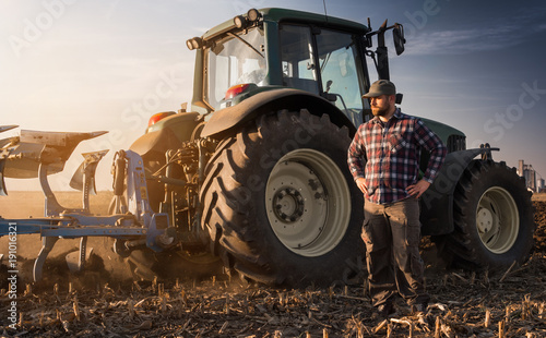 Foto Farmer working during the tractor plowing fields -preparing land for sowing in a