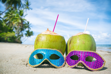 Colorful sequined carnival masks and fresh green coconut drinks on a palm fringed beach in Brazil