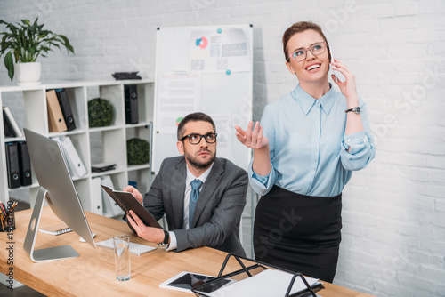 businessman trying to work while his colleague talking by phone and annoying him Wallpaper Mural