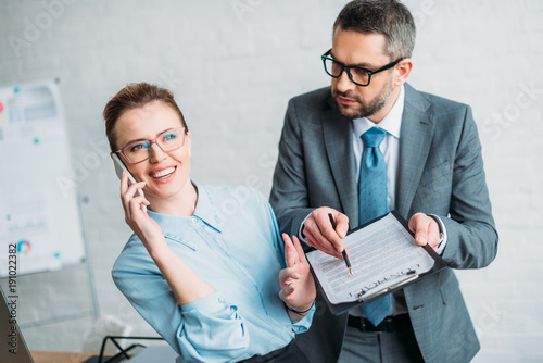 Photo businessman asking his colleague to sign document while she talking by phone and