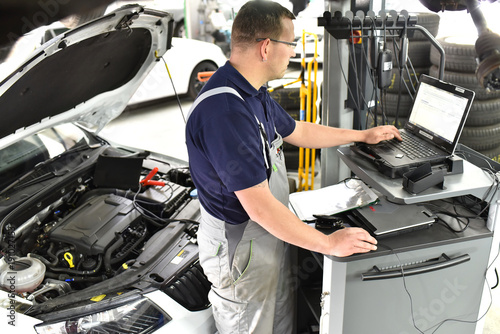Mechaniker in der Autowerkstatt beim Softwareupdate mit einem Diagnosecomputer in der Werkstatt am Auto durch einen Mechaniker // Mechanic in the car repair shop during software update