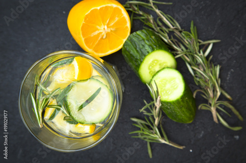Glass jar of detox water with lemon, cucumber and a spring of rosemary and ingredients on the table, black stone background, top view