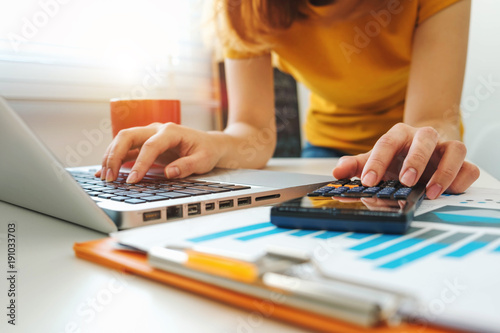 Fotografía  businesswoman hand working with finances about cost and calculator and laptop wi