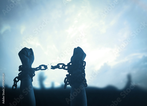 Obraz International day for the remembrance of the slave trade and its abolition concept: Silhouette human hands raising and broken chains at night background. - fototapety do salonu