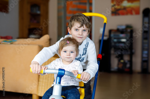 af5f4efc166 Little kid boy pushing bycicle or tricycle with cute baby sister. Toddler  girl and brother