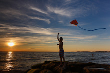 Boy Launches A Kite On The Sea...