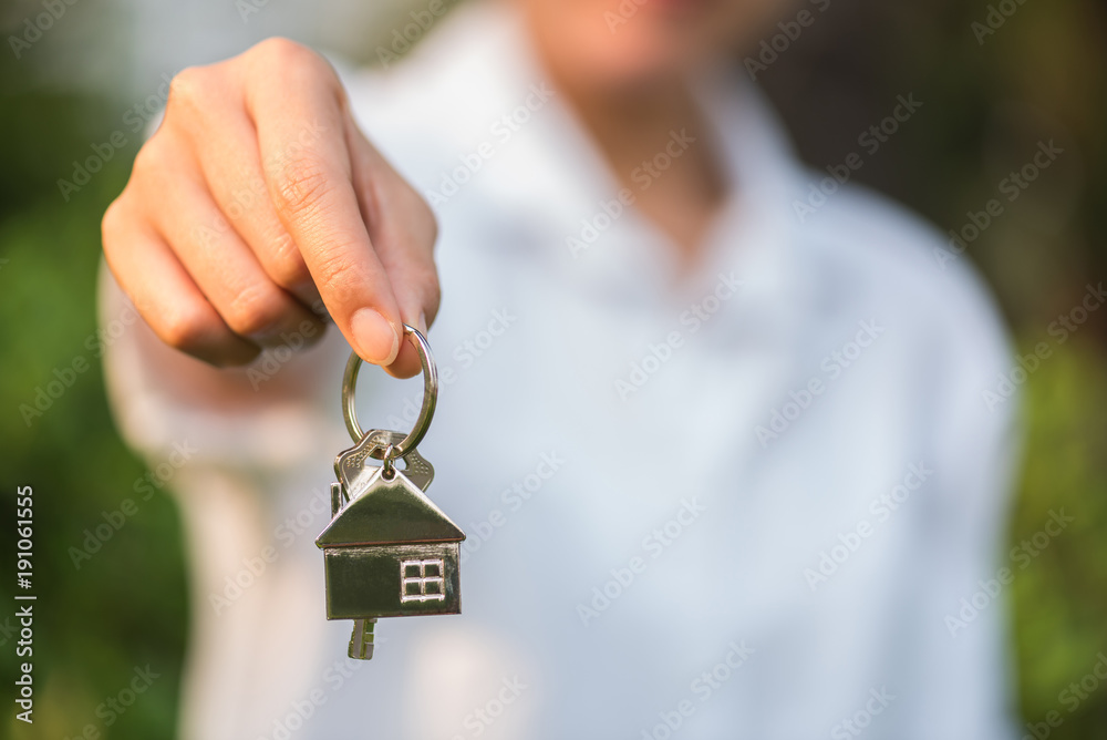 Fototapety, obrazy: house key in woman hand and green leaves background
