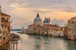 Landscape sunset view of traditional Gondolas on famous Canal Grande with historic Basilica di Santa Maria della Salute in the background in romantic golden evening light at sunset in Venice,
