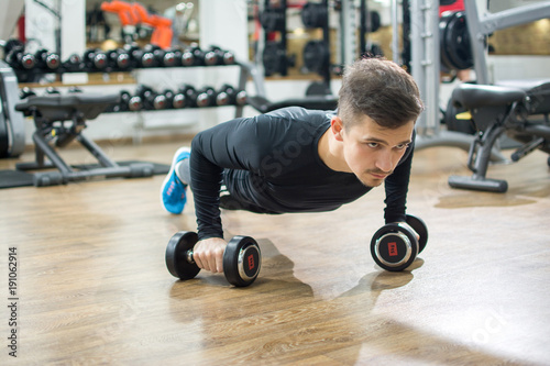 Foto op Plexiglas Fitness Young handsome man doing push-up exercise with dumbbells.