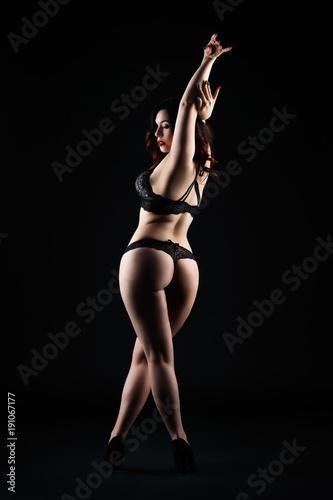 Deurstickers Akt Beautiful sexy woman in lingerie posing on black studio background, low key studio shot