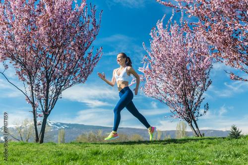 Frau macht Fitness Jogging auf Hügel zwischen Kirschbäumen die blühen