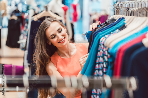 Obraz Frau sucht nach Kleid auf Kleiderstange im Mode Laden und sieht glücklich aus - fototapety do salonu