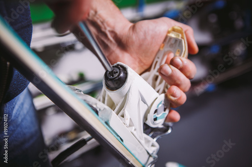 Theme tincture and repair ski equipment ski. Close-up of a Caucasian man's hand use a hand-held screwdriver tool to tweak, twist bindings for ski boots in the workshop