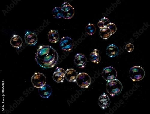 Rainbow soap bubbles on black background. Canvas Print