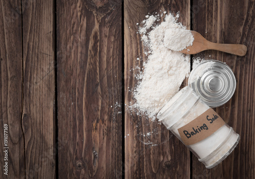 Photo Jar of baking soda with text space on wood background,top view
