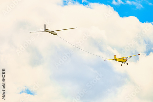 Yellow small light-engine sport plane flying in the cloudy sky pulls on a rope the glider plane