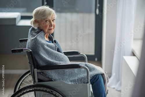Fotografie, Tablou  Cheerless senior female sitting in invalid chair in front of the window