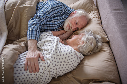 Pleased Elderly Couple Lying In Bed Old Woman And Man Looking At
