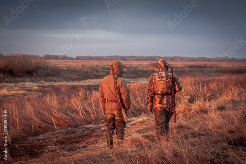 Tuinposter Jacht Hunters hunting in rural field during sunrise. Field painted with orange color of rising sun