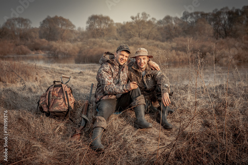 Aluminium Prints Hunting Hunter men friends resting in rural field during hunting period symbolizing strong friendship