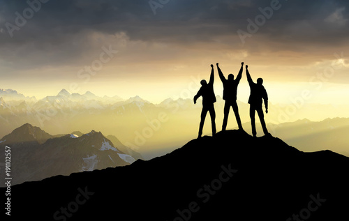 Photo Stands Mountaineering Silhouettes of team on mountain peak. Sport and active life concept.