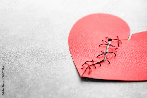 Fotografia Paper heart cut in half and sewn back together on light background