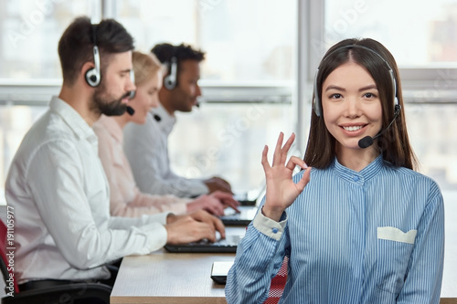 Call center operator with okay hand sign gesture Wallpaper Mural