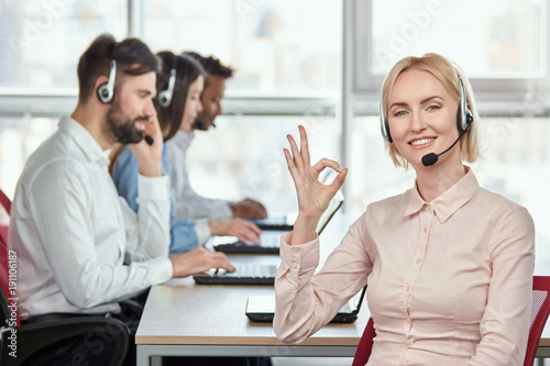 Blond female operator with headset shows okay gesture Canvas Print