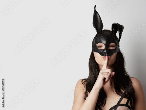 Fotografie, Obraz  Sexy woman wearing a black mask Easter bunny standing on a white background