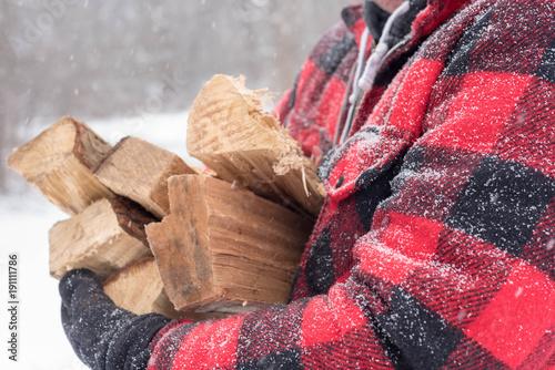 Photo Closeup of man carrying bundle of firewood through the snow