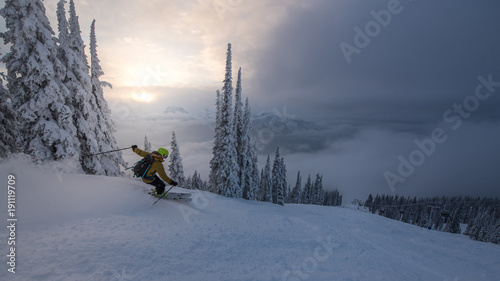 Fotografie, Obraz  Skier in brown jacket and green helmet alone in resort just before sunset
