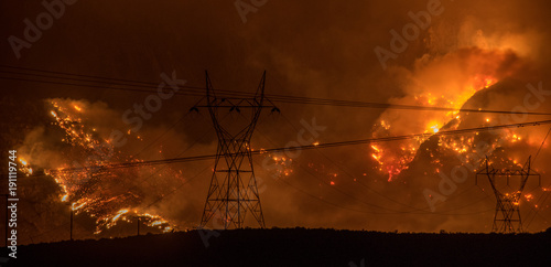 Fotografía Large wildfire in California on hillside behind silhouette of powerlines