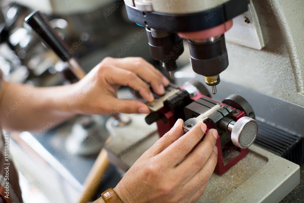 Fototapety, obrazy: Workman making duplicates of keys .