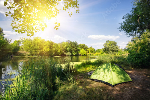 Foto op Plexiglas Blauwe hemel Green tent on the river bank in the bright sun