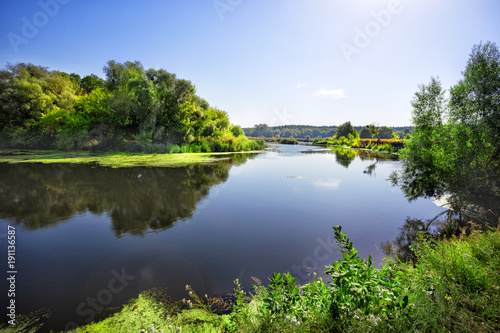 Spoed Foto op Canvas Grijze traf. Sunny day on the river with green trees on the shore