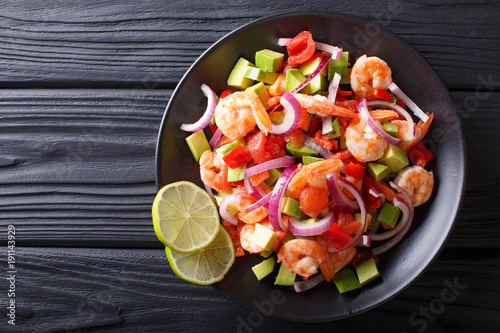 Delicious ceviche of shrimp with vegetables, spices and lime close up on a plate. horizontal top view