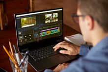 Freelancer Video Editor Works At The Laptop Computer With Movie Editing Sofware. Videographer Vlogger Or Blogger Camera Man At Work Editing Vlog. Tracking And Revealing Shot