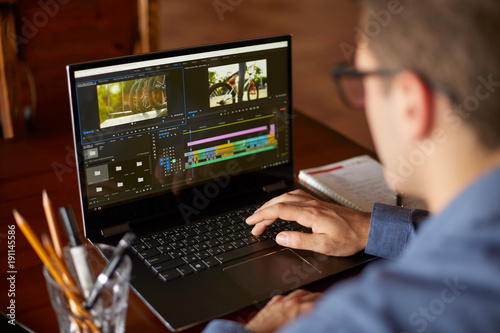 Fotografia  Freelancer video editor works at the laptop computer with movie editing sofware