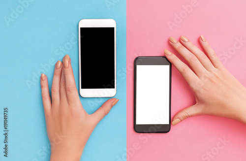 Photographie  female hands hold two phones black and white.