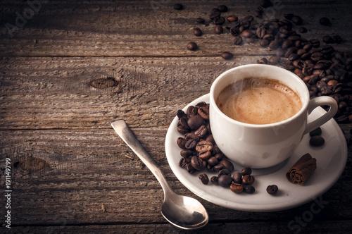 Filiżanka kawy na drewnianym stole z cynamonem